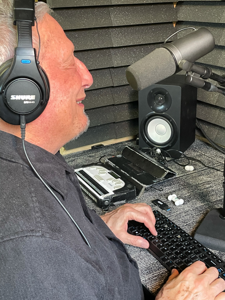 Michael Moran in a recording studio speaking into a microphone with his hands on a computer keyboard.