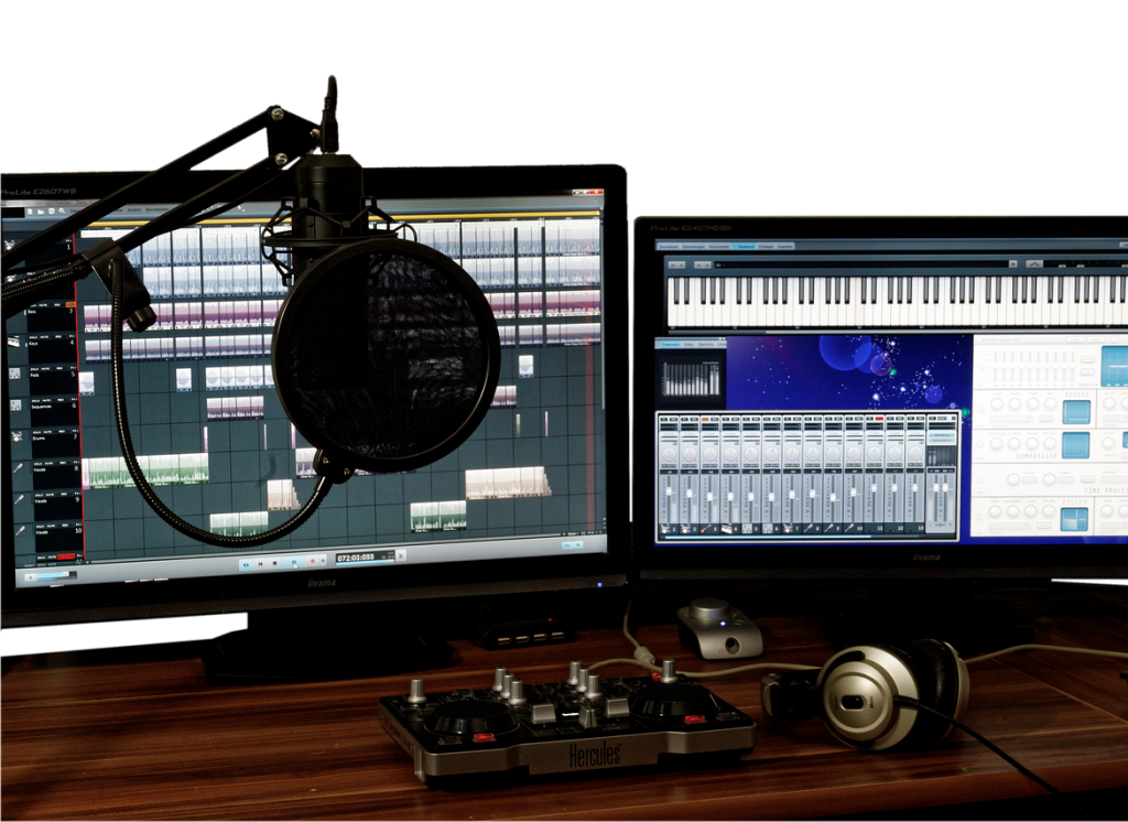 In the foreground various pieces of audio recording and mixing equipment are on a table. In the background two computer monitors can be seen with audio editing software open